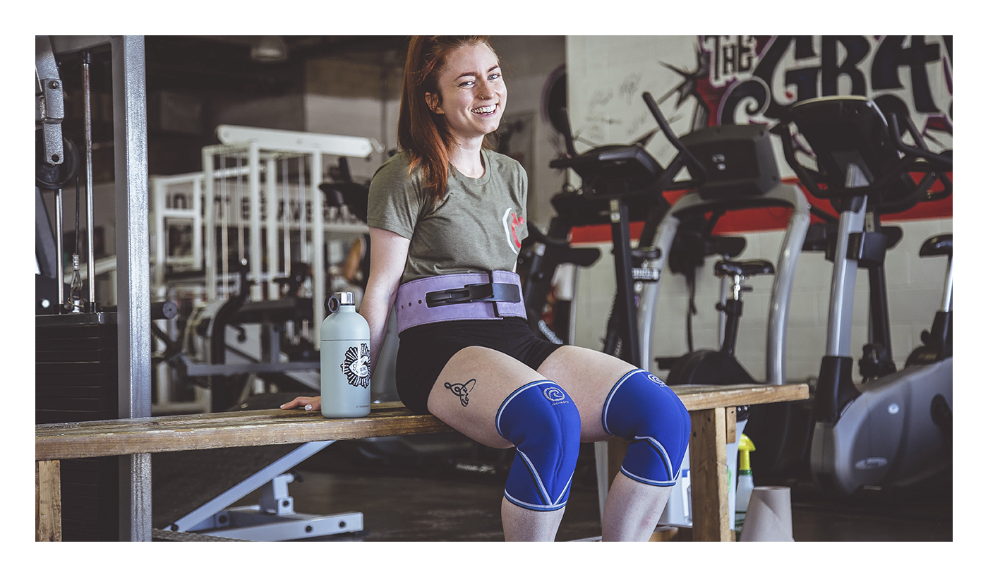 A woman in weightlifting gear, sitting on a bench at the gym, showing the benefits of collagen for easing joint pain