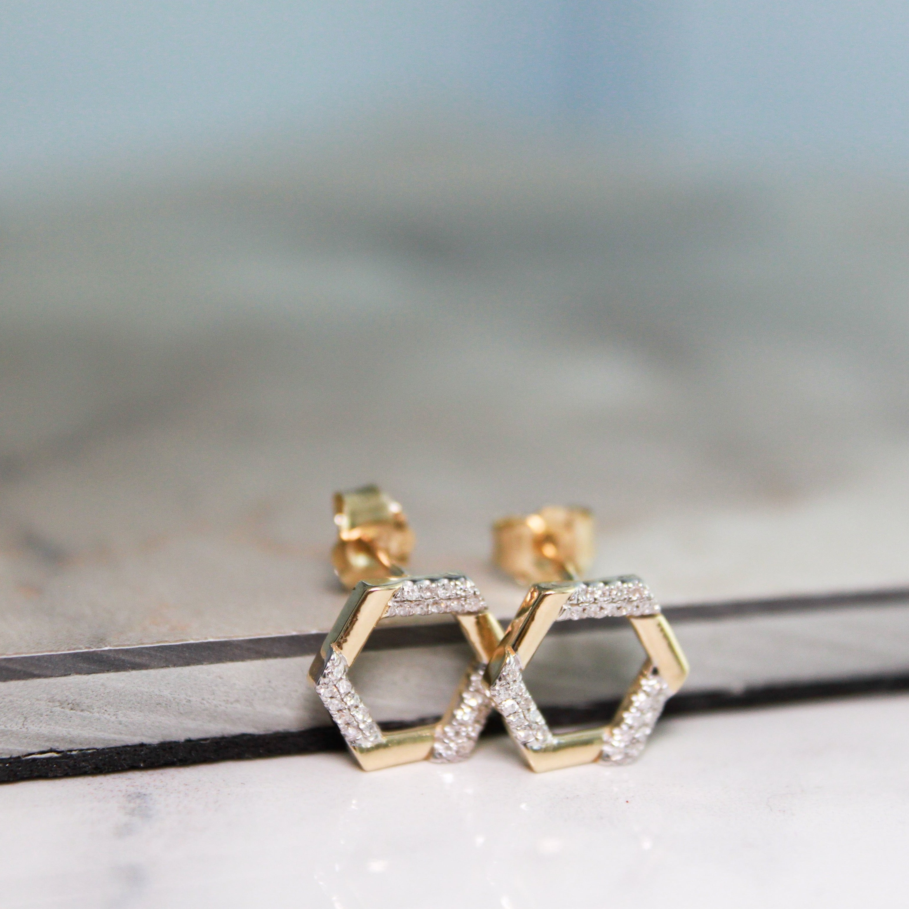 Pair Yellow Gold Hexagon Natural Diamond Earrings positoned on shelf