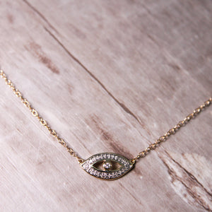 Solid Yellow Gold Evil Eye Necklace on laying on wooden surface