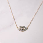 Solid Yellow Gold Evil Eye Necklace hanging on gold chain in fron of white background