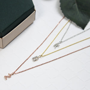 3 Solid gold initial necklaces in yellow gold, rose gold and white gold on white background