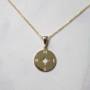 Yellow solid gold necklace pendant in shape of a compass on white background