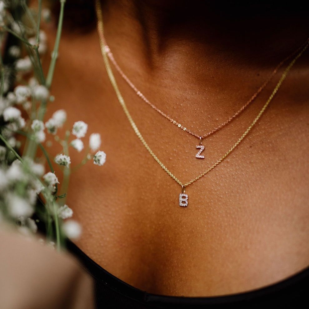 Woman wearing two initial necklaces solid gold with diamonds on neck