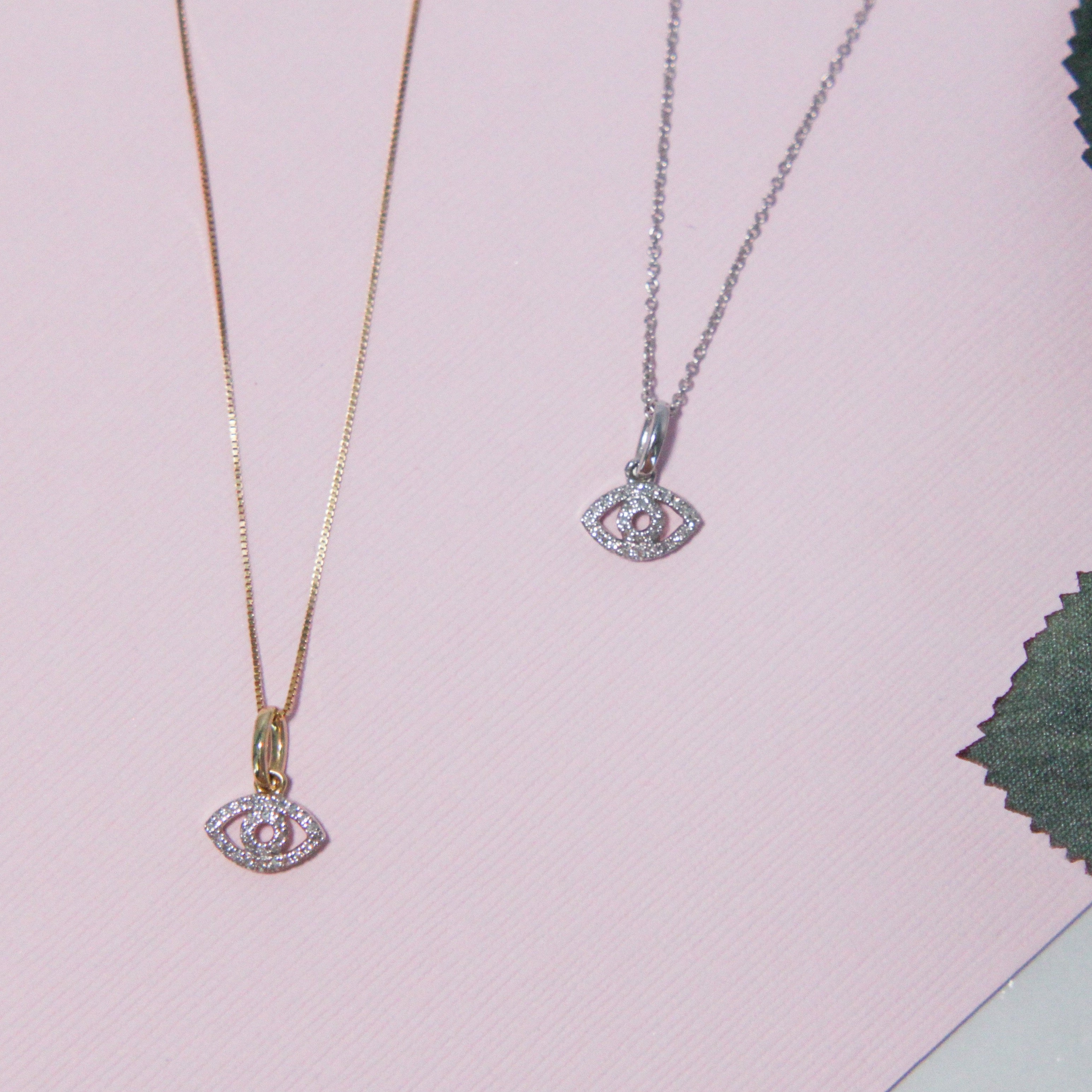 Two Evil eye gold and diamond necklaces on pink background