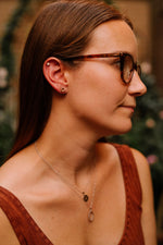 star earrings with cubics and knot earrings on model wearing two chains