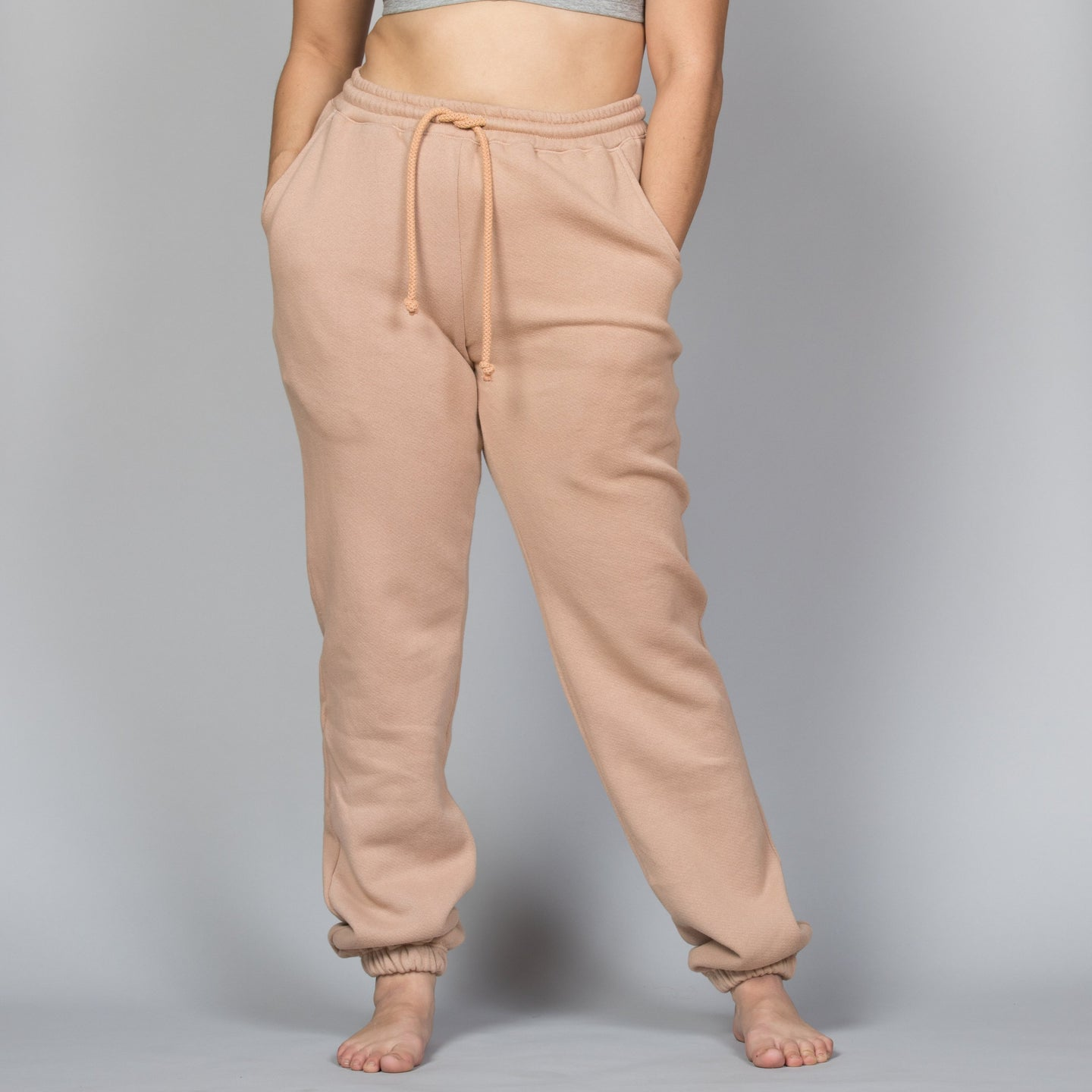 person with hand in pockets of light pink sweatpants