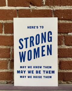 cream colored poster with blue letters says here's to strong women, may we know them, may we be them, may we raise them