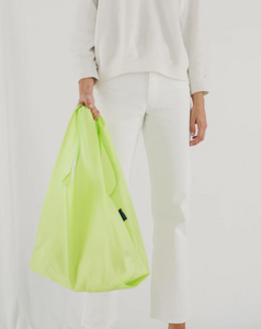 lime colored bag hanging from hand