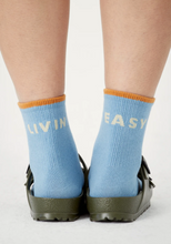 Load image into Gallery viewer, view of sky colored crew socks on feet from behind