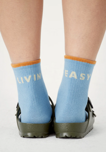 view of sky colored crew socks on feet from behind