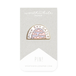 "half domed enamel gold pin. white arc reads ""pink sky gazer"" with pink clouds and lilac sky in open space"