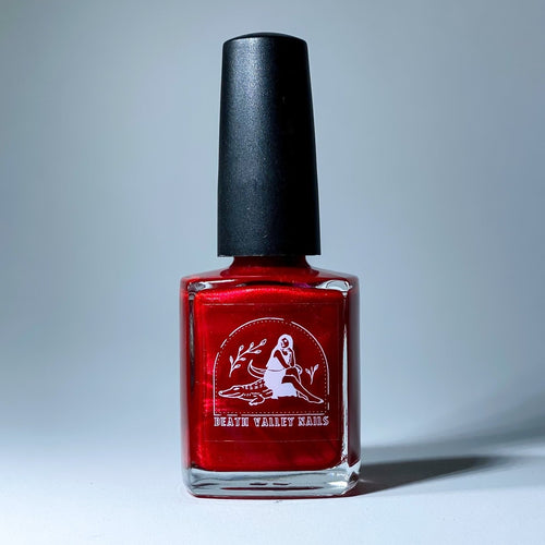glass bottle of red nail polish