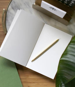 Open blank notebook on marble tray. gold pen laying on page