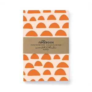"Cream notebook with orange half domes all over cover. Brown paper band over center reading ""Notebook, screen printed cover - 100 blank unlined pages"""