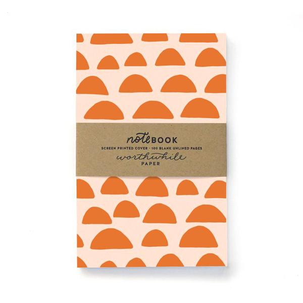 Cream notebook with orange half domes all over cover. Brown paper band over center reading