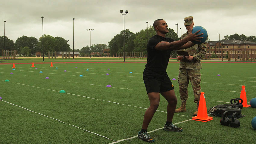 Soldier back-throwing a medicine ball for ACFT