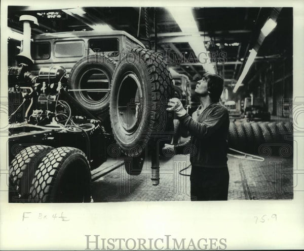 1977 Press Photo Worker Handles Tire in Production Line of Kamaz Trucks, Russia - Historic Images