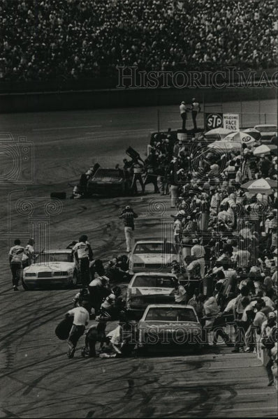 1984 Press Photo Cars take pit stops while caution flags fly at race, Alabama - Historic Images