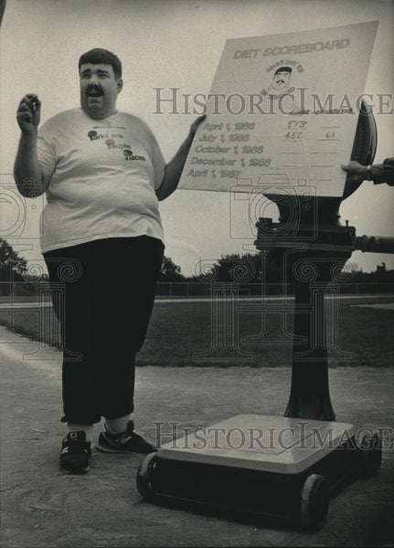 1986 Press Photo David Schultz with a large scale showing weight loss, Milwaukee - Historic Images