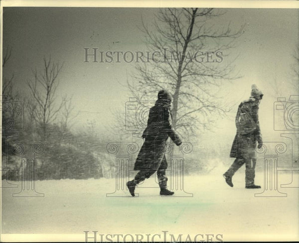 1987 Press Photo Two people walking along highway T during snowstorm in WI - Historic Images