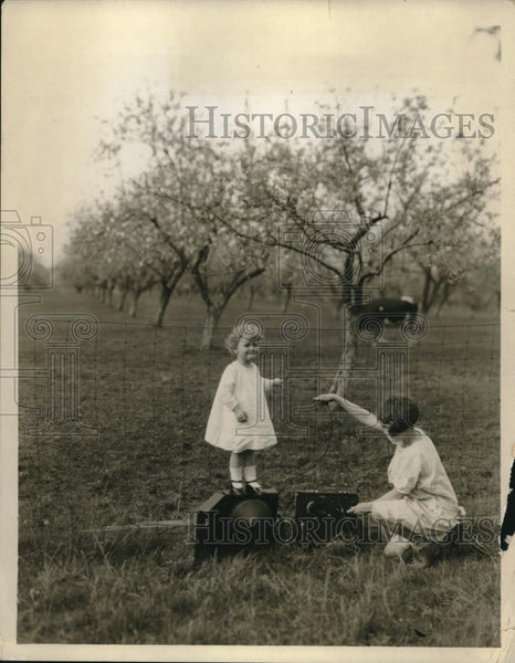 1925 Press Photo A woman & child with a radio set in an orchard - Historic Images