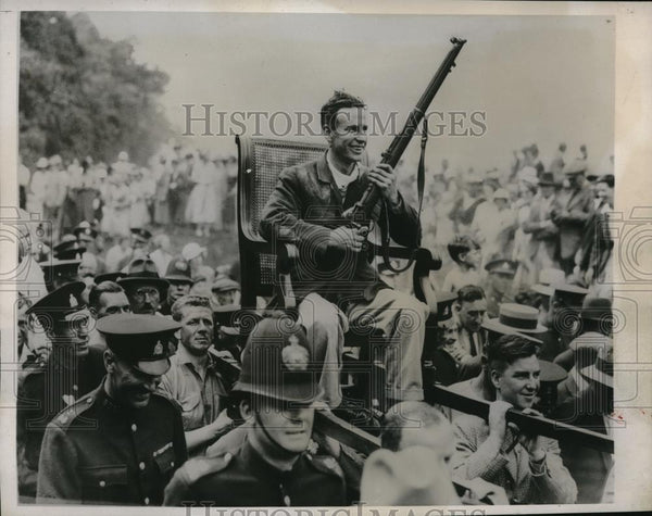 1933 Press Photo Winning Nimrod DE Woods Carried By In Chair With Rifle - Historic Images