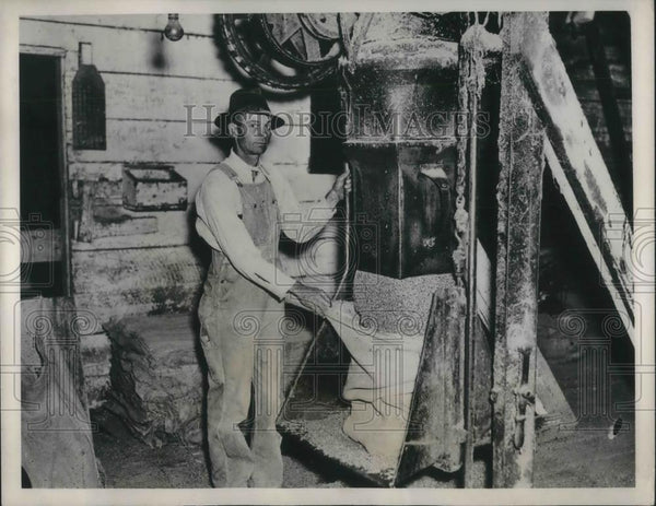 1937 Press Photo Block of cotton comes out of a cotton gin, seed hulls for stock - Historic Images