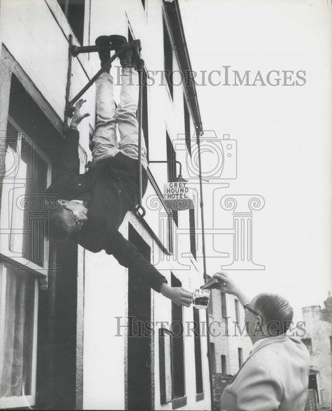 Press Photo Terry Andrews just hanging around upside down outside his bar - Historic Images
