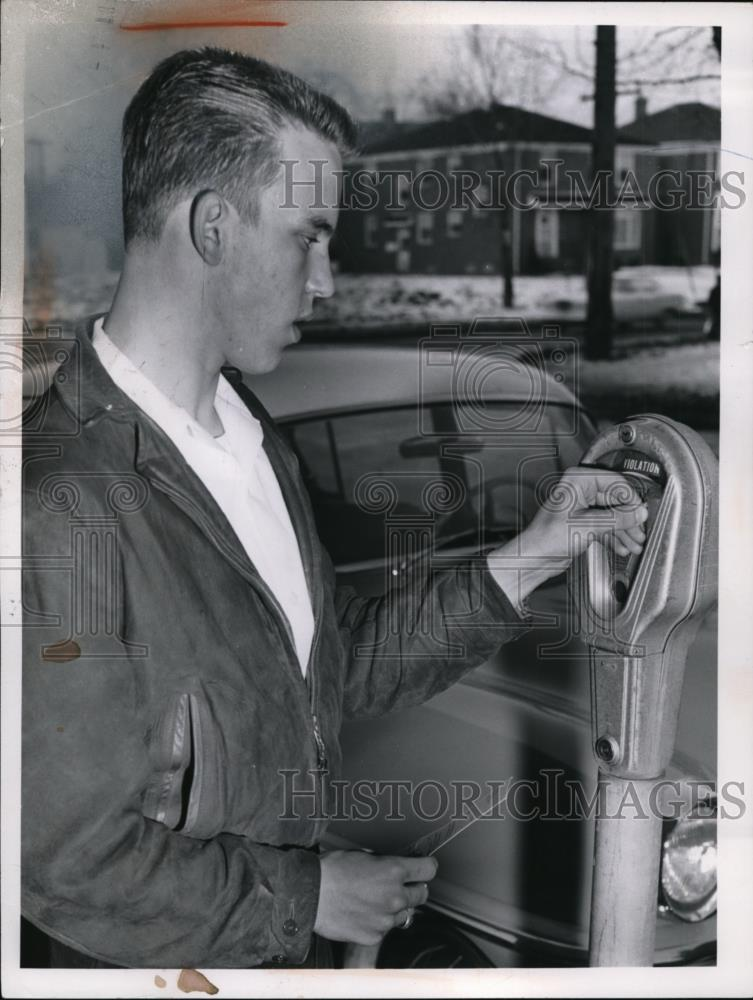 1959 Press Photo Ed Schuler places a coin in a parking meter in Shaker  Heights