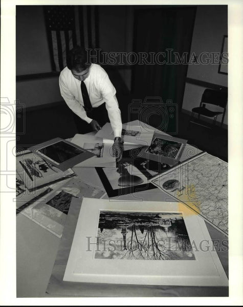 1991 Press Photo Kermit Pike shows rare prints for the Western Reserve auction - Historic Images