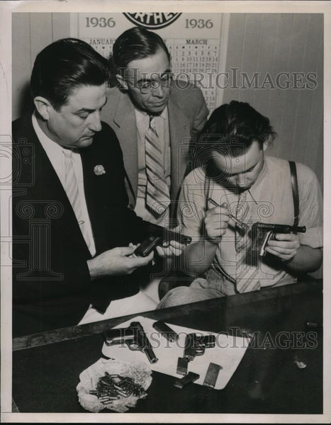 1936 Press Photo Clarence Larkin inspecting guns with Bureau of Identification - Historic Images