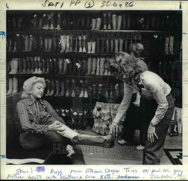 Press Photo Shari Rugg Of Athena Tries On Boots With Kathi Zolman, Manager - Historic Images