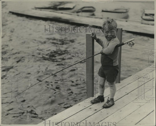Press Photo Young Boy Fishing off a Dock in the Fresh Air and Sunshine - Historic Images
