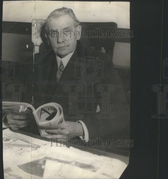 1924 Rev HC Lilaus sits opens book pose reads - Historic Images