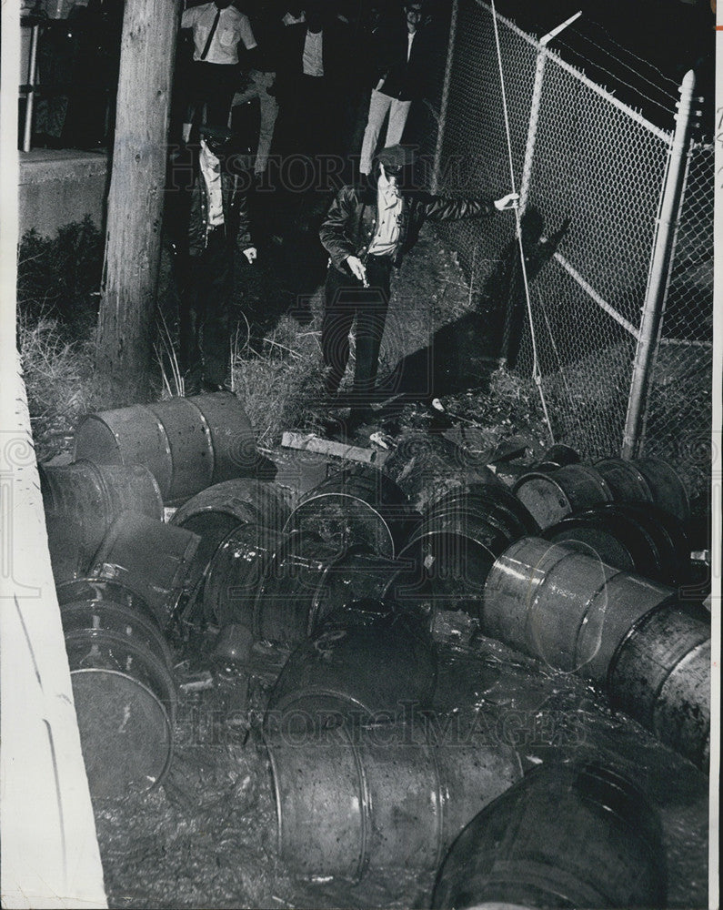 1965 Press Photo Policemen Gene Gray & Fred Stevenson check oil drums swept by floods - Historic Images
