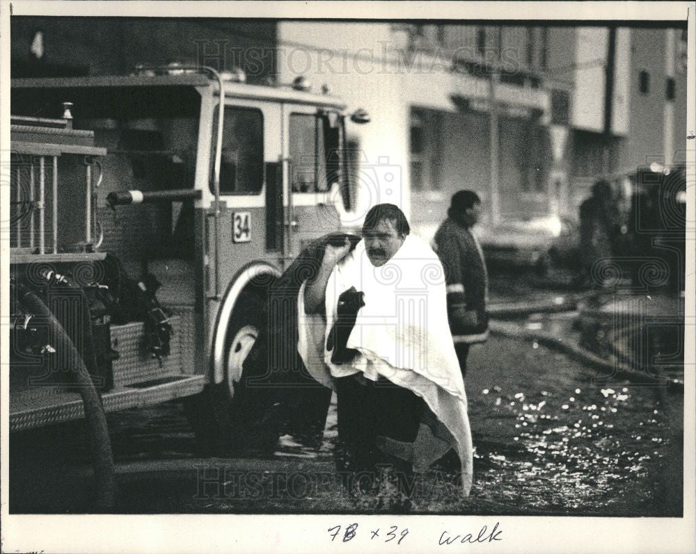1987 Press Photo Fire Fighter Soaked Burning Warehouses - Historic Images