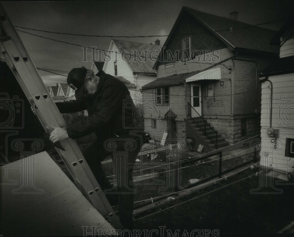 1993 Press Photo Building Inspector Lloyd Schneider climbs down from a roof - Historic Images
