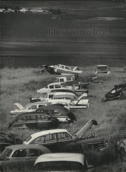 1976 Press Photo Beyond these junked cars is the site of the proposed plant - Historic Images