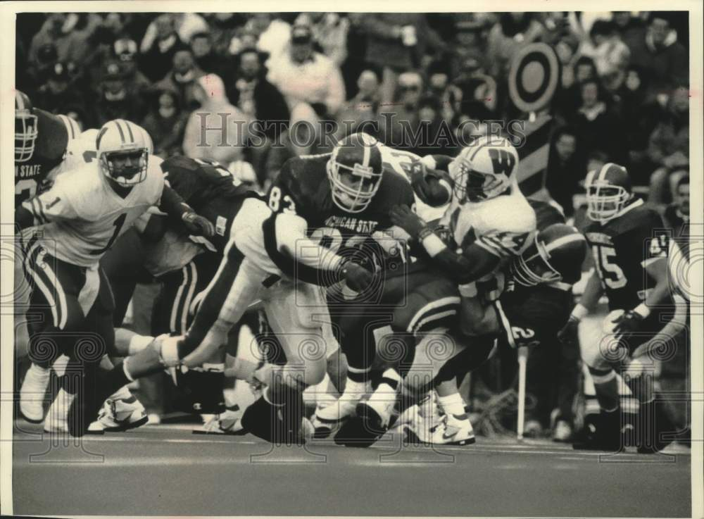 1992 Press Photo Wisconsin back Jason Burns gets tackled by Michigan defense - Historic Images
