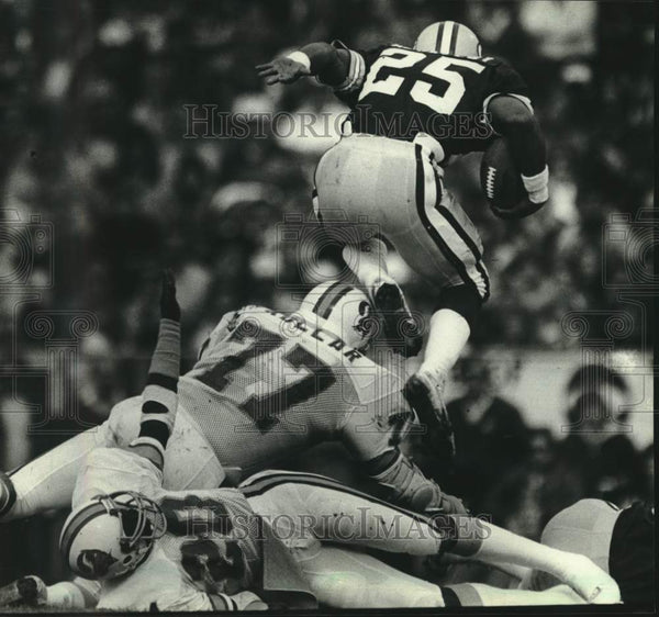 1981 Press Photo Green Bay Packers' Harlan Huckleby leaps over player, football - Historic Images