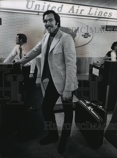 1973 Dick Cunningham at the ticket counter at the airport - Historic Images