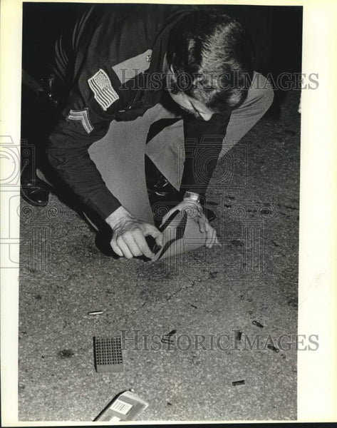 Press Photo Police detective Fred Balmos picks up spent shell casings - Historic Images