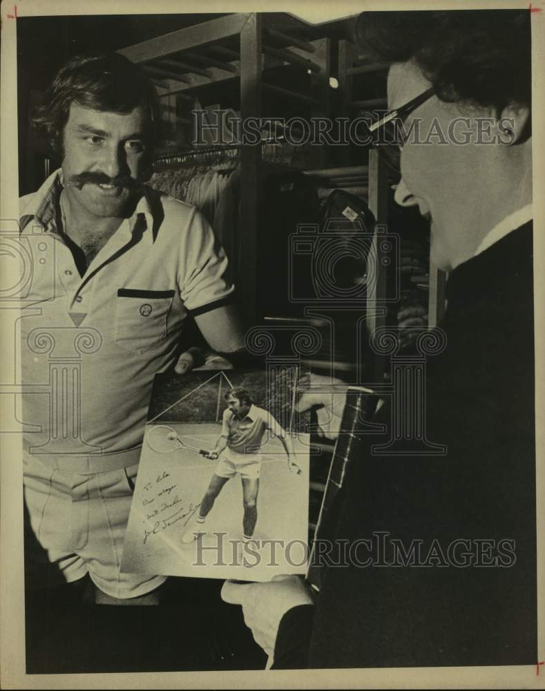 Press Photo Tennis player John Newcombe presents an autographed photo - Historic Images