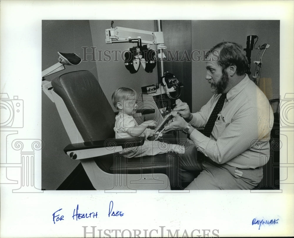 1988 Press Photo Dr. Stephen Maher, ophthalmologist, check's on patient's eye - Historic Images