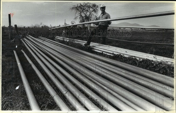 1987 Press Photo Dave Simonson stacks irrigation pipes on Hayden Lakes farm - Historic Images