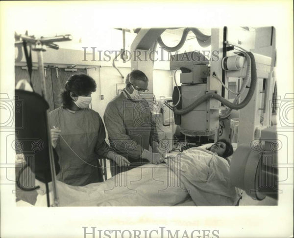 1985 Press Photo Arthur J. Wendte performs a catheterization on unknown patient. - Historic Images