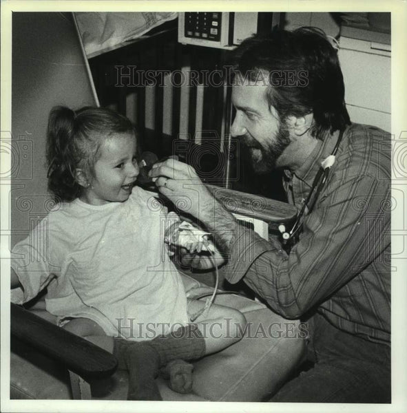 1990 Press Photo Steve Jones, Pediatric nurse, is shown examining a young girl - Historic Images
