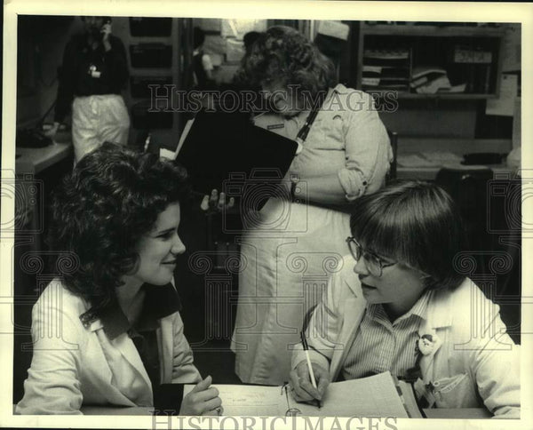 1986 Press Photo Nurses complete paperwork at St. Peter's Hospital, Albany, NY - Historic Images