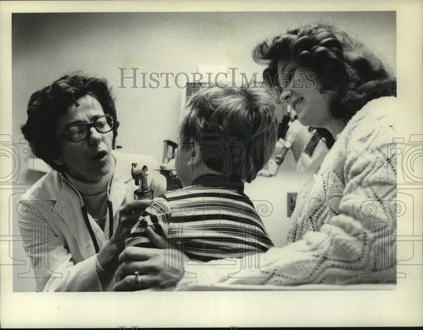 1976 Press Photo Sister Lucy Cresanti examines toddler in Albany, New York - Historic Images