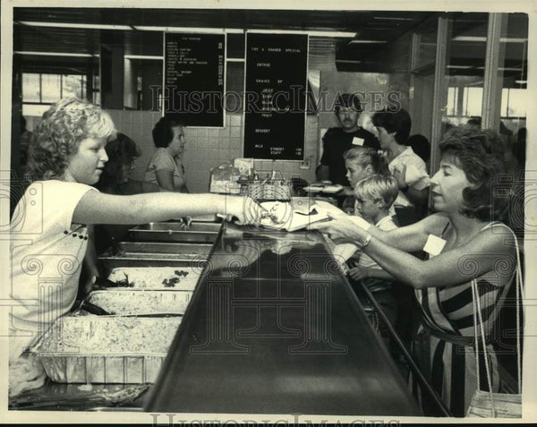 1984 Press Photo Albany, New York High School student serves food at picnic - Historic Images